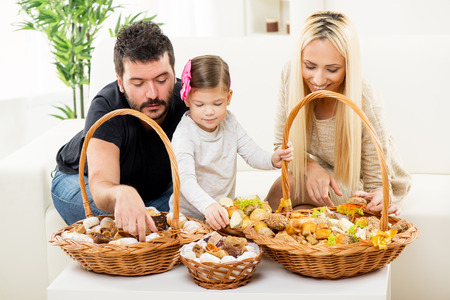 hairclip: Happy family together, parents with daughter sitting on the couch in the living room in front of woven baskets filled with pastry, choosing the next snack.