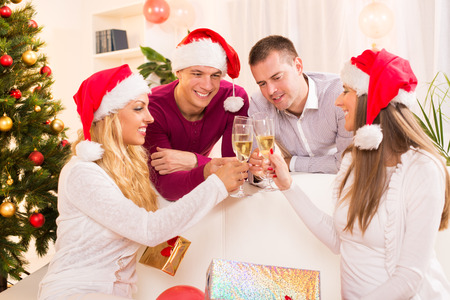 Happy friends Celebrating Christmas or New Year with glass of champagne in home interior. photo
