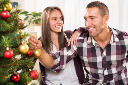 home decorating: Happy young couple enjoy decorating Christmas tree at home.