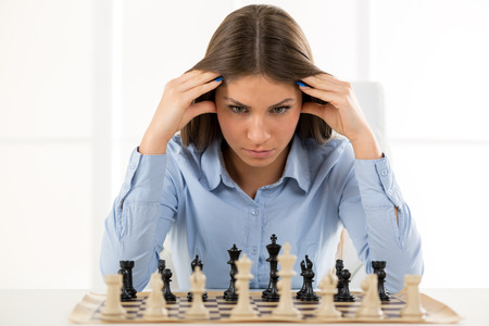 A young businesswoman is sitting in front of a chess board and thinking staring at the figure, holding hands on her head. Foto de archivo