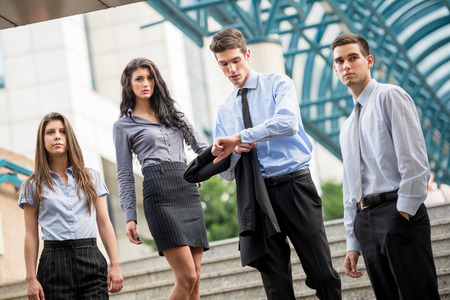 formally: Small group of business people, formally dressed, standing on the steps of the office building as if expecting someone, while a young businessman looking at his watch in his hand. Stock Photo