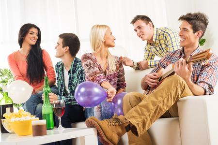 Een kleine groep jongeren rondhangen in de house party, praten met elkaar, terwijl hun vriend plezier spelen akoestische gitaar.