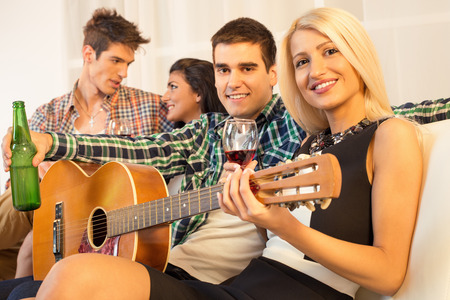 Small group of happy young people hang out at the house party with an acoustic guitar. photo