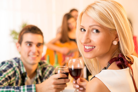 The young beautiful girl and young guy knocking the glasses toasting with wine while in the background in the ambient house parties see the girl who plays acoustic guitar. photo