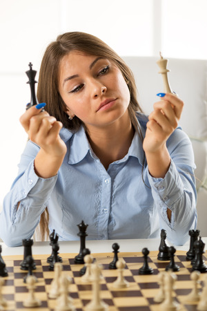 chessmen: Young businesswoman sitting at the table in front of a chess table, staring at the chessmen of white and black king.