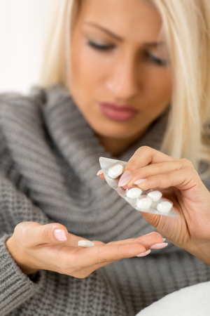 painkiller: Close-up of female hands with long nails holding a  medicine, face blond girl is out of focus.
