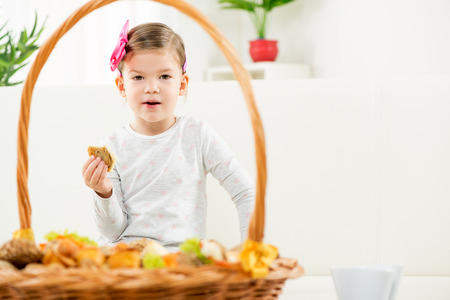 hairclip: Portrait of cute little girl with hairclip, eating pastry, front wicker basket filled with tasty baked goods.