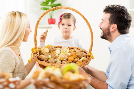 hairclip: Young parents kneel in front of their little daughter with a smile watching her eat pastries from a large woven basket which together hold in their hands.