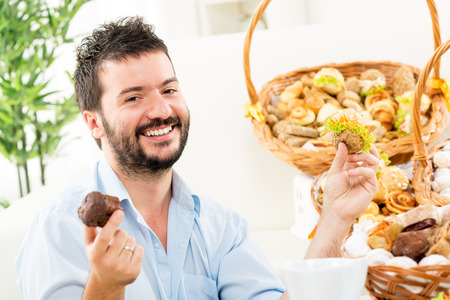 A young man with a beard, holding in his hands a sweet and savory pastries. With a smile looking at the camera. In the background you can see woven baskets with pastries. photo