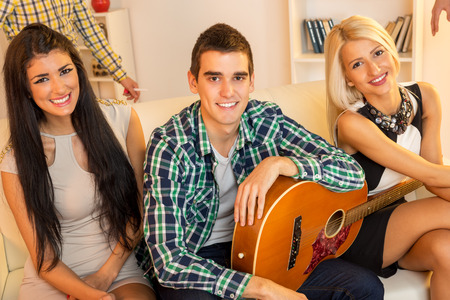 Young guy with an acoustic guitar at house party, sit on the couch between two pretty girls. With a smile looking at the camera. photo