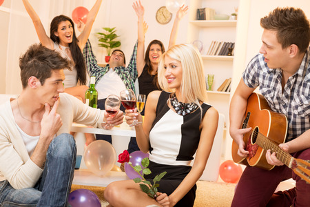 courting: A young guy is courting the pretty girl at home party, while their friend plays acoustic guitar, and in the background the rest of society with arms raised celebrated their relationship. Stock Photo