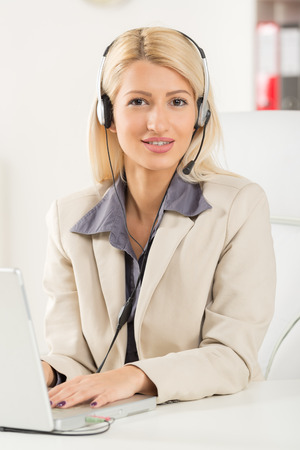 handsfree device: Young beautiful blonde girl, elegantly dressed, sitting at an office desk in front of laptop with a headset on her head. With a smile looking at the camera. Stock Photo