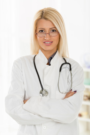 white coat: Young cute blonde female  doctor with the glasses, dressed in a white coat standing arms crossed with a stethoscope over the neck, with a smile looking at the camera. Stock Photo