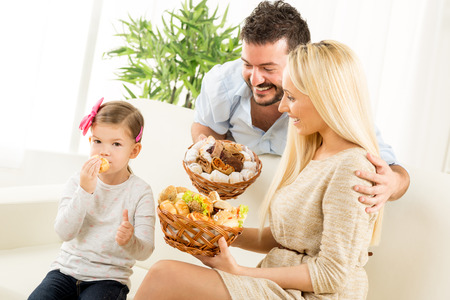 hairclip: Young parents hold in their hands woven basket with delicious salty and sweet pastries. Beside them sit on the couch their little daughter eating pastries and holding thumb-up. Stock Photo