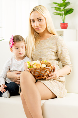 hairclip: A beautiful young mother gives a wicker basket with fresh baked products to her daughter by offering her a variety of delicious baked goods. With a smile looking at the camera.