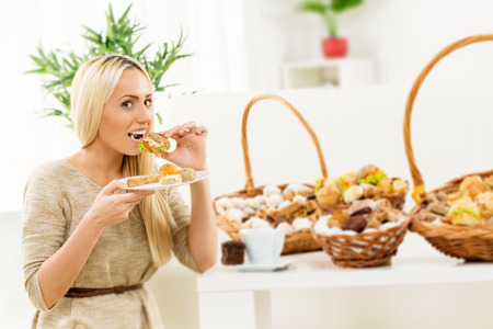A young pretty blond girl eating a small sandwich, in the background you can see woven basket with bakery products.