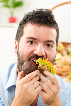 Close-up of a young man with a beard who greedily pushed into the mouth pastries and looking at the camera. In the background is woven basket with pastries. photo