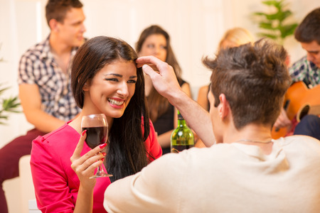 The young man at the house party is courting the pretty brunette caressing her hair, and in the background you can see a small group of young people having fun at a party. photo