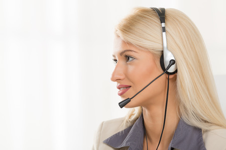 handsfree device: Portrait of pretty young blonde woman dressed elegantly with a headset on her head.