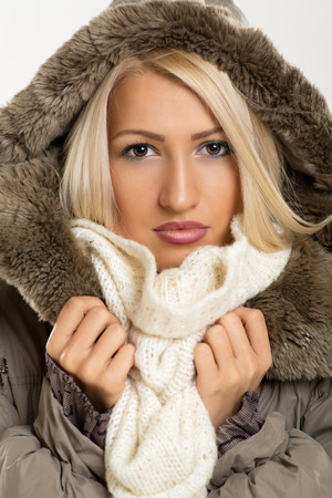 Beautiful blonde girl in winter jacket with fur hood, looking at the camera. Stock Photo