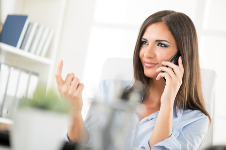 horny: A pretty business woman at her workplace telephoning with a mobile phone and with a seductive look on her face beckoning with finger.