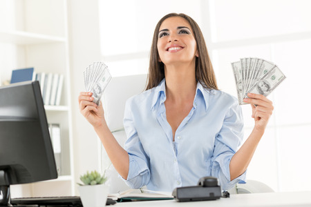 Young businesswoman in office, sitting at an office desk, holding money and with an expression of happiness on her face looking up. Banque d'images
