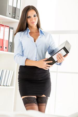 falda corta: Empresaria bonita joven en una falda corta, la celebraci�n de una carpeta y sonriente mirando a la c�mara. Foto de archivo