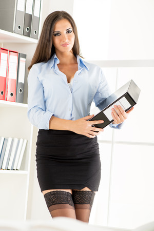 businesswoman skirt: Young pretty businesswoman in a short skirt, holding a binder and smiling looking at the camera.