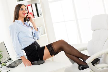 secretarias: Empresaria bonita joven en una falda corta que se sienta en un escritorio de oficina con los pies sobre una silla de oficina y llamar por tel�fono.