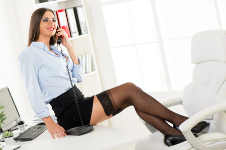 Young pretty businesswoman in a short skirt sitting on an office desk with her feet up on a office chair and phoning.