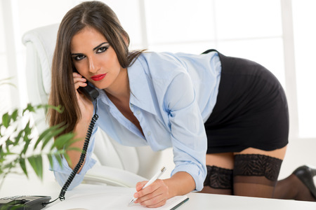 mujer arrodillada: Una mujer joven y bonita en una falda corta, de rodillas en una silla de oficina, apoy�ndose en el escritorio de la oficina, llamando y escrita en el planificador. Foto de archivo