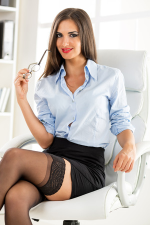 business woman legs: A young attractive woman in a short skirt, sits cross-legged in office armchair, holding glasses and smiling looking at the camera. Stock Photo