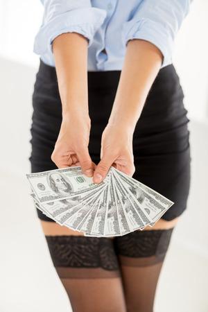 mini falda: Mujer irreconocible en mini falda en manos extendidas sosteniendo billetes de d�lar. El foco est� en los billetes de banco. Foto de archivo
