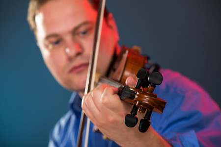 virtuoso: Close-up of violin in the hands of the violin virtuoso with a face out of focus.