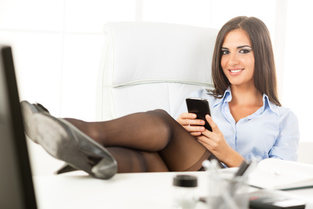 Pretty businesswoman in the office sitting on a  office chair with her feet up on the table, holding a cell phone with a smile looking at the camera.