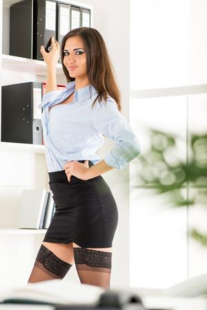 secretaria sexy: Mujer de negocios bastante joven en una falda corta de pie delante de estantes con las carpetas y con una sonrisa mirando a la c�mara.