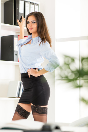 Pretty young business woman in a short skirt standing in front of shelves with binders and with a smile looking at the camera.