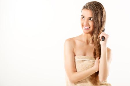 jeune fille adolescente nue: La jeune fille avec une serviette enroul�e autour de sa poitrine, peigner ses longs cheveux bruns avec une brosse � cheveux. Banque d'images