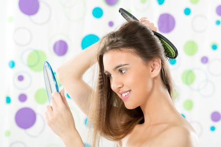 jeune fille adolescente nue: Fille tenant un miroir dans lequel ressemble et peignant ses longs cheveux bruns.