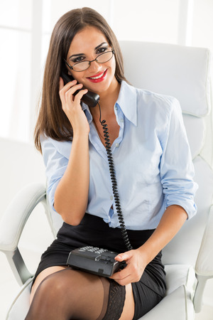 secretary skirt: A young pretty businesswoman with glasses sitting in the office chair and phoning, holding the phone in her lap, smiling looking at the camera.