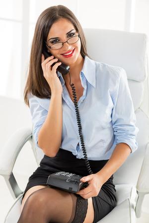 secretaria sexy: Una joven empresaria bonita con gafas sentado en la silla de la oficina y llamar, sosteniendo el tel�fono en su regazo, sonriendo mirando a la c�mara.