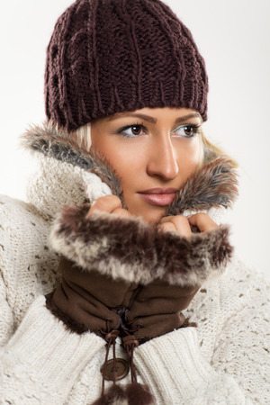 Beautiful young girl In winter clothes with a wool cap and fur gloves, sticks to the fur collar In which is tucking.