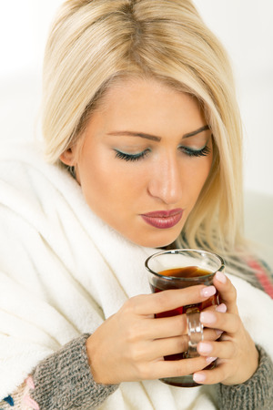 Beautiful blonde girl sits tucked in a blanket, holding a cup of tea in which blows. Stock Photo