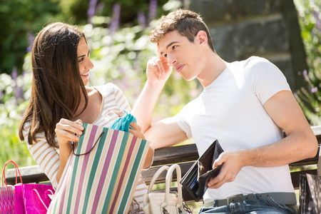 empty wallet: Young guy with an empty wallet in his hand with a worried expression on his face and his girlfriend who sits on a park bench next to a bunch of shopping bags.