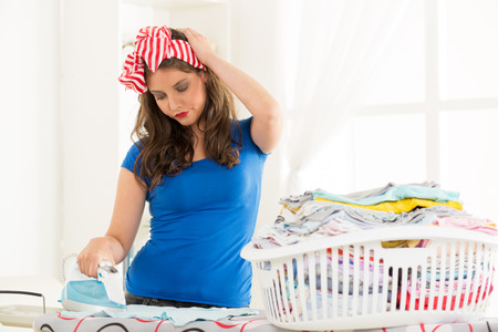 dissatisfaction: Young woman ironing on ironing board, in front of her is full laundry basket, with an expression of dissatisfaction with one hand holding her head.