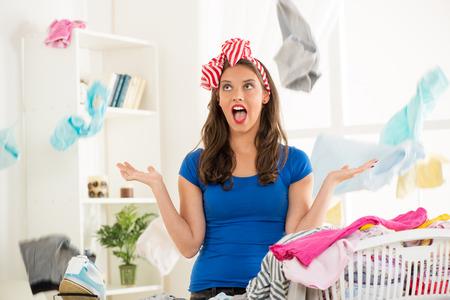 Ama de casa frustrada joven de pie en frente de la tabla de planchar y dispersa la lavandería del cesto de la ropa.