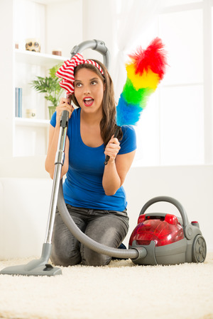stereotypical: A young housewife kneeling beside the vacuum cleaner with duster in hand, satisfied with the good work cleaning up the house.