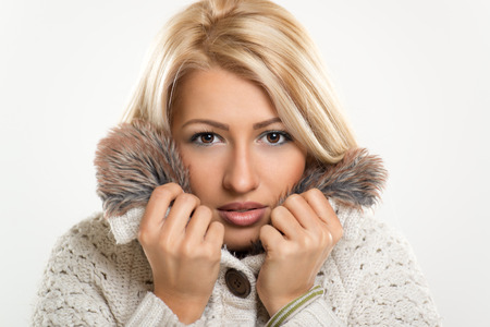 Close-up of beautiful young blond girl in winter clothes, sticks to her fur collar, in which is tucking.