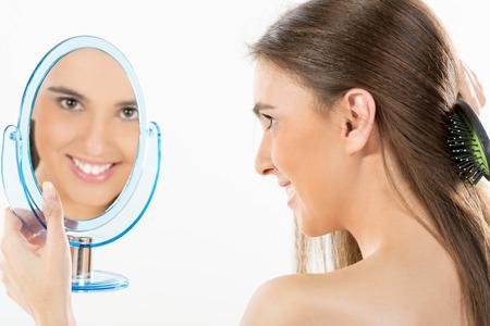 jeune fille adolescente nue: Fille tenant un miroir dans lequel ressemble et peignant ses longs cheveux bruns. Reflet d'une jeune fille dans le miroir regardant la cam�ra avec un sourire.