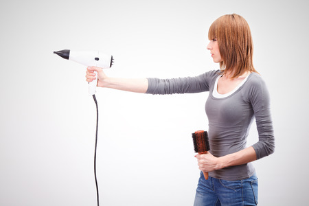 hair dryer: Beautiful young hairdresser holding a hair dryer like a gun and brush for hair